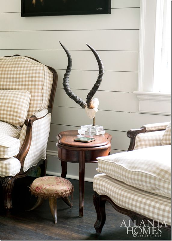 A Pair Of Check Covered Antique Club Chairs And An Antelope Antler Stand  Create A Striking Grouping In This French Inspired Abode.