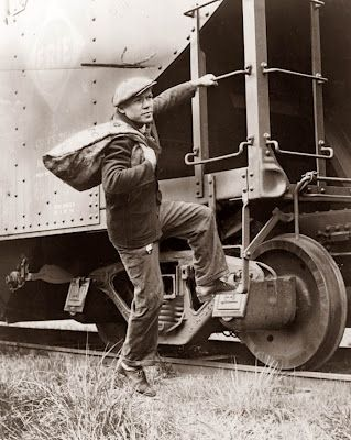 """A Hobo hopping a freight train. The picture was taken in 1935, which would have been at the depth of the Great Depression. Many men would hop freights hoping to get somewhere that they could find work. So often times """"Hobo"""" was not synonymous with """"Tramp"""". Often Hobos were displaced workers traveling trying to find some type of work."""