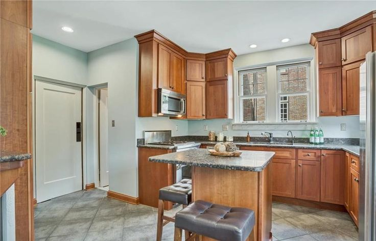 Renovated kitchen with shaker style maple cabinets, granite counters, Jenn-Air appliances, center island & adjoining breakfast room.