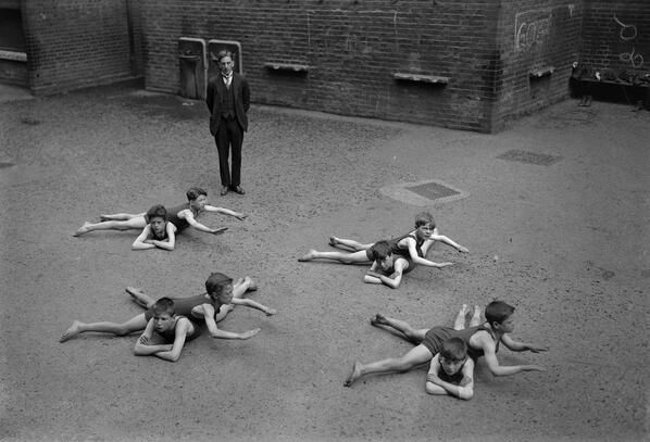 Children learn to swim in the schoolyard in England, circa early 1920s