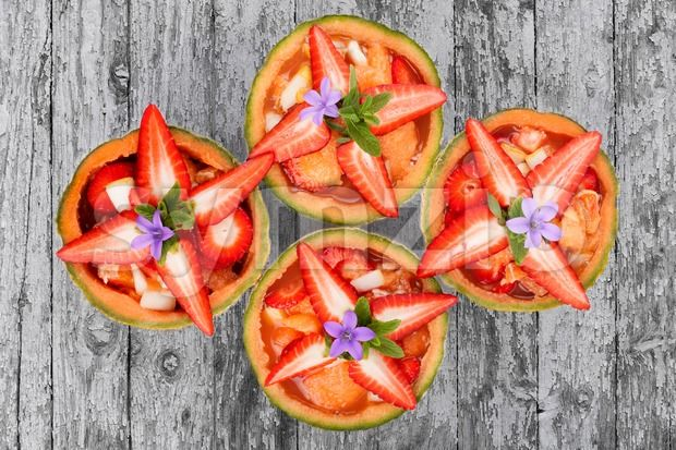 Stock photo of Strawberry Melons from $1.99. Fruit salad inside melons decorated with fresh strawberries and mint...