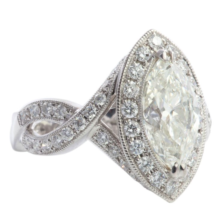 Hand made 18K white gold marquise cut engagement ring. The center features an elongated 2.15 ct. marquise diamond surrounded with a milgrain edge & round diamond accents. We make this ring for stones greater than 1.00 carat, and any shape of diamond. *Price does not include center diamond. $3,300.00