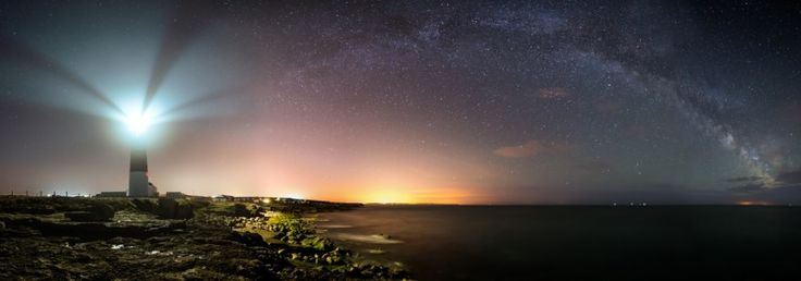 Late spring and the Milky Way arcs over the Dorset Jurassic Coast viewed from Portland Bill lighthouse