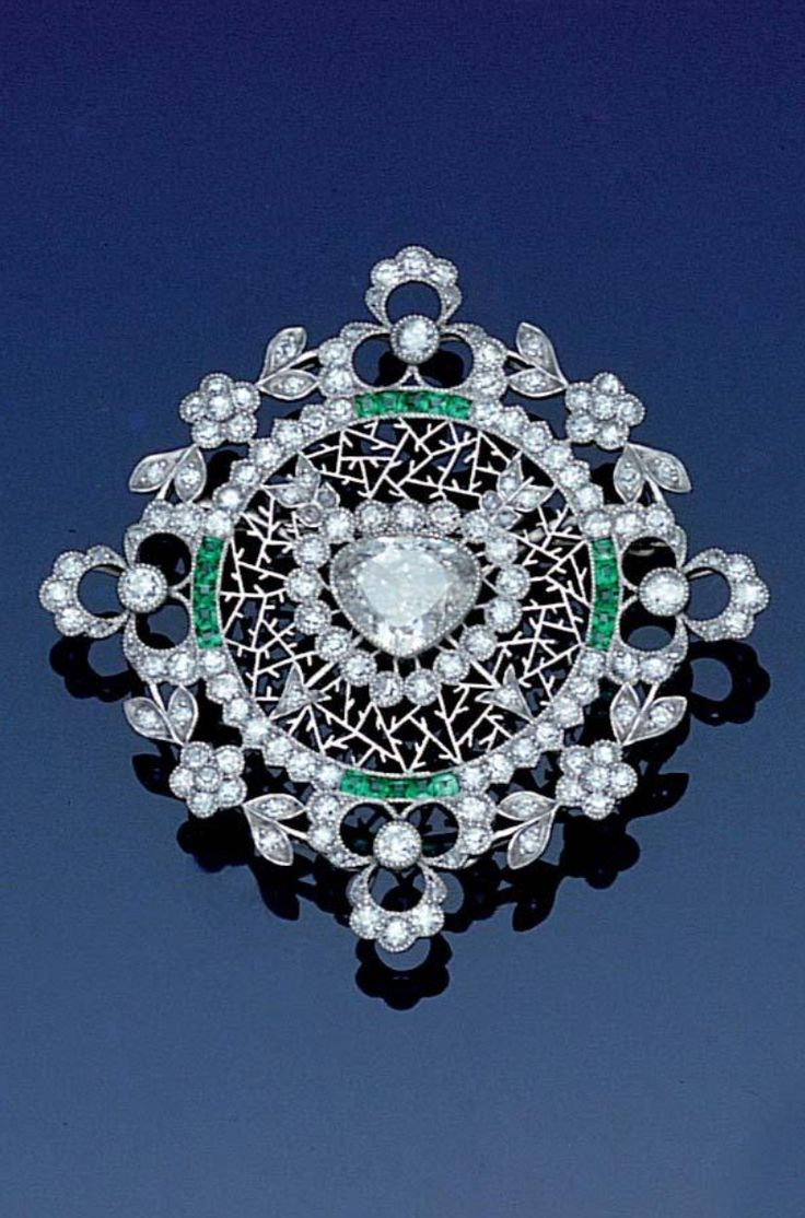 A Belle Epoque diamond and emerald brooch, circa 1905. Designed as a stylised snowflake, the central triangular-cut diamond framed by circular and rose-cut diamonds, calibré-cut emeralds and finely pierced platinum icicles, within a floral wreath border of old brilliant and single-cut diamonds, partial maker's mark and assay mark, both probably French, diameter 4.3cm.