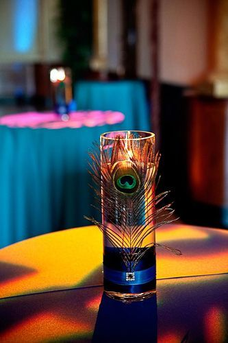 Simple, peacock centerpiece; Glue pretty ribbons holding peacock feathers to a glass vase and light up with a floating candle!