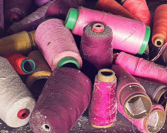 Urban decay photography featuring spools of threads that were left behind when…