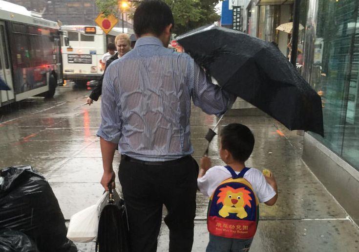 Deze foto van een vader die zelf compleet natregent, maar zijn zoon droog houdt, gaat viraal op social media.