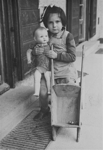 A young Jewish DP girl poses with a doll and toy stroller in the Feldafing displaced persons camp.