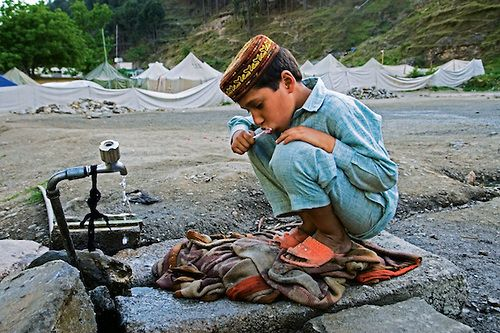 © Annie Griffiths | A finales de 2005, un terrible terremoto devastó el norte de Pakistán, matando a más de 75.000 personas e hiriendo gravemente a mucho más.  Balakot se molió cero.  Una ciudad próspera de 30.000 fue completamente aplastada.  El número de muertos fue desgarrador.  La población está regresando, pero la amenaza de terremotos adicionales ha causado el gobierno paquistaní para considerar el cierre de todo el valle.  Un niño se lava los dientes fuera del campo de refugiados.