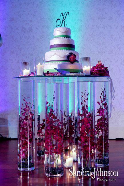 Una presentación única de una torta de boda sobre una mesa con bases de jarrones cilíndricos adornados con flores sumergidas en su interior. #CentroDeMesa