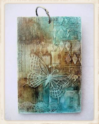 By Guriana. Stencils, gesso, gel medium, Glimmer Mist, butterfly punch. Love the colors and textures!