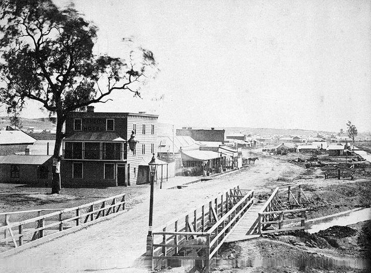 """Bridge Streets Dai Gum San precinct . The earliest known photograph in 1857 . In the foreground is the Bendigo Creek and the bridge for which the street was named.On the corner is the three story Bendigo Hotel, later the site of the late 19th century brick Showgrounds Hotel. Beyond the hotel can be seen the row of """"Harney's Buildings"""".The Golden Dragon Museum was constructed on the site in 1990."""