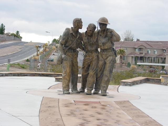 """The Bataan Death March Memorial in Las Cruces, New Mex., features American and Filipino Soldiers supporting each other during the march. Footprints leading to and from the statue """"look back to what has passed, down to what is present and ahead to what might be,"""" according to notes by the sculptor, Kelley Hestir. """"The footprints are symbolic of the many soldiers who began the march and the few who finished. The impressions were made from the feet of those who survived,"""" Hestir said."""