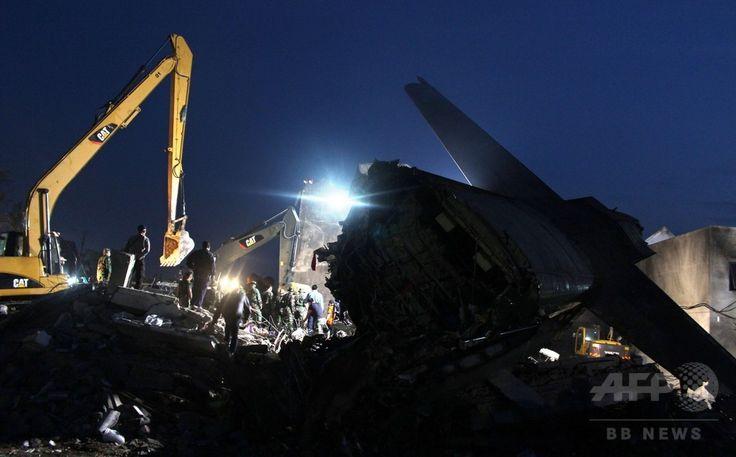 インドネシア・スマトラ島メダンで、空軍輸送機が墜落・炎上した現場で作業にあたる救助隊員ら(2015年7月1日撮影)。(c)AFP/ATAR ▼1Jul2015AFP|インドネシア軍機墜落、死者141人に http://www.afpbb.com/articles/-/3053313