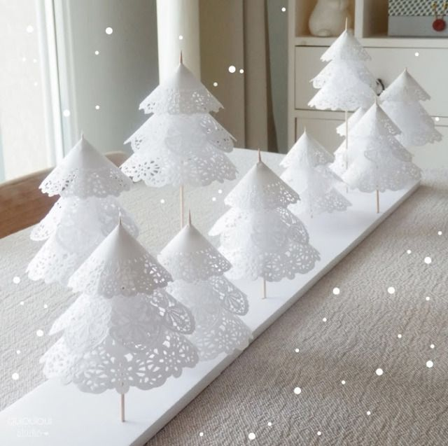 What a cute idea! Paper doilies + wooden skewers stabbed through a foam board = snowy, adorable forest.