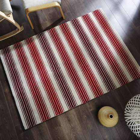 Designed with a pattern of stripes in varying widths over a natural background, this patterned rug is crafted from 100% wool and is available in a choice of colours and sizes.
