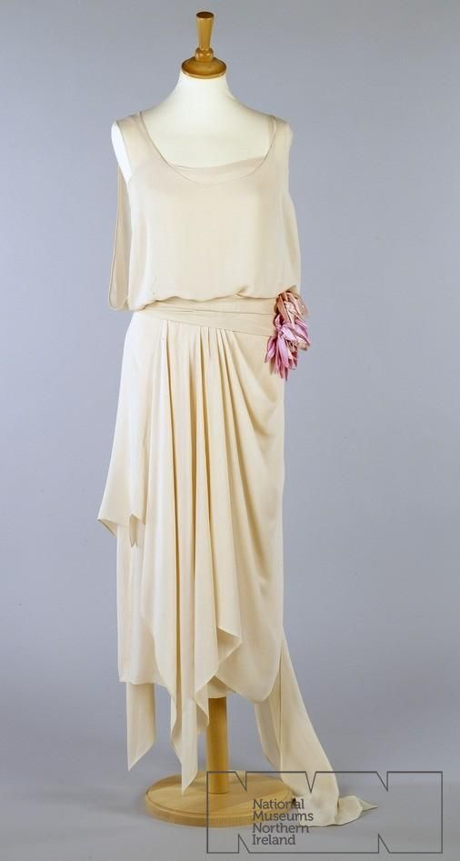 National Museums Northern Ireland - 1920s Evening dress of pale pink silk crepe, sleeveless. low back joined at waist. Dress has under-dress has ribbon straps,hooked opening left side seam. Overdress has bodice draped to waist with open side seam, skirt gathered and draped to handkerchief point at front right hip with long floating panel from backleft left hip which extends to train on floor.