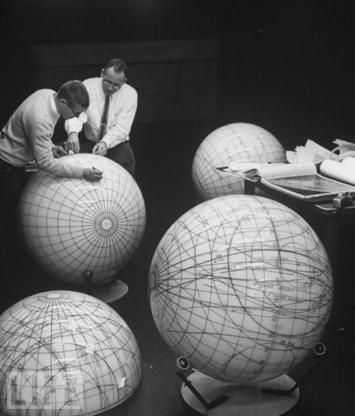Scientists study the phases of the moon on lunar models in preparation for an eventual manned flight to moon, February 1962. Photographer: Fritz Goro