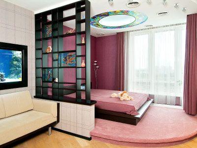 низкая кровать возле окна, стеллаж-перегородка, не перекрывающая солнечный свет, цветовое зонирование