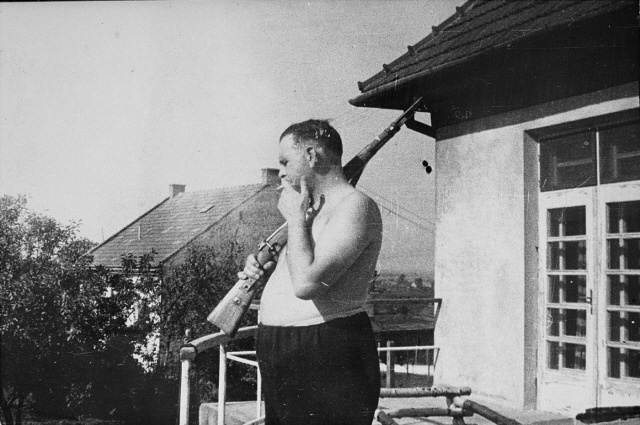 Commandant Amon Goeth (played by Ralph Fiennes in the film Schindler's List) stands half dressed with his rifle on the balcony of his villa in the Plaszow concentration camp.  After the war, Goeth was tried by the Polish Supreme Court and executed in 1946.