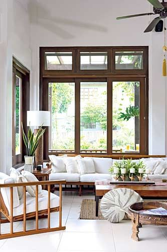 Sunlight streams in through the generous glass windows and doors. A sofa made of wood and laden with white cushions paired with matching armchairs makes for a comfortable living area. A low coffee table sits atop The owner says that, while many of the furniture pieces are antiques, most of the accessories are new.