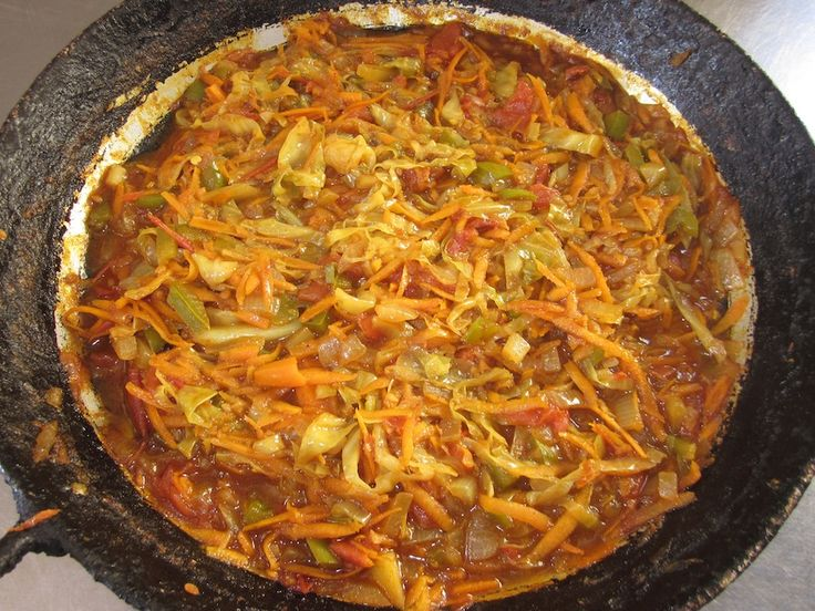 This extremely spicy dish is called chakalaka (as in don't-eat-it-by-itself-because-your-mouth-will-catch-fire-and-explode spicy). It is a relish made of vegetables and spices, served with pap or bread (to tone down the spice). There are many different variations on recipes; each family makes it a little differently.