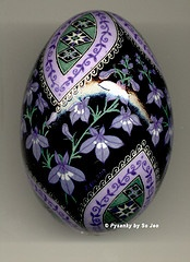 This pysanka displays  the flowers of the lily of the valley, generally depicted arrayed along a stem.  Flowers represent beauty in nature and life.