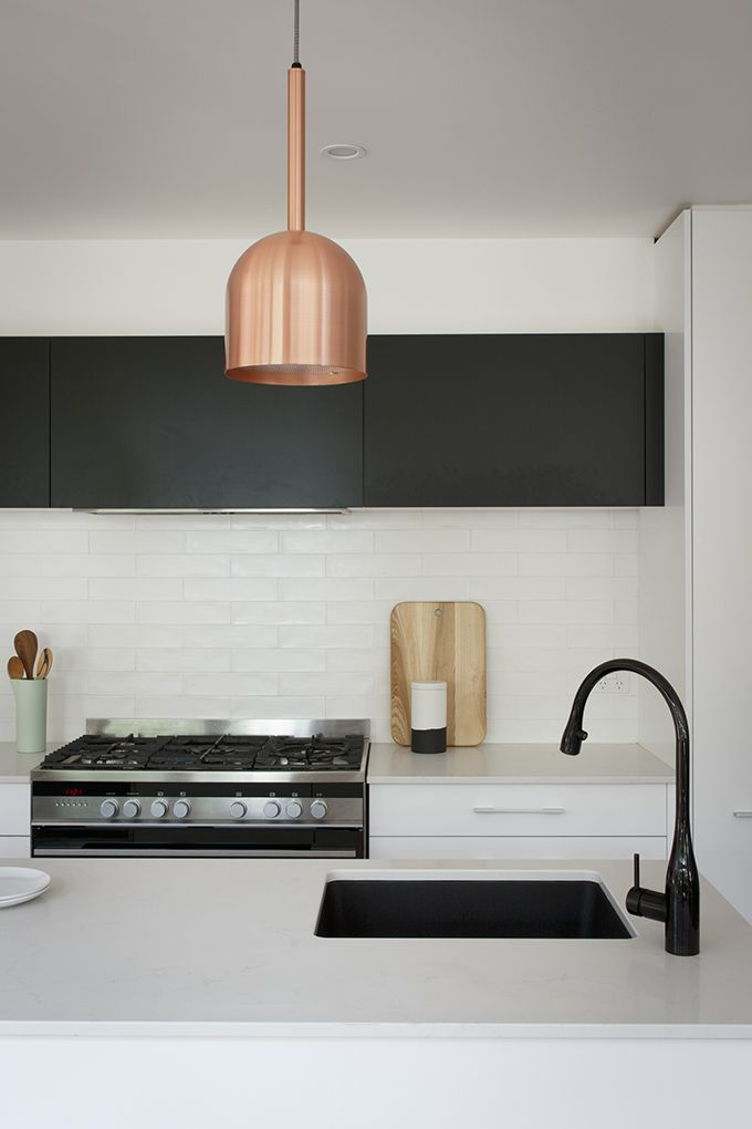 MODERN SCANDI: A traditional Scandi base of white cabinetry with black feature overheads and hints of copper adds a bold, modern edge. Featuring:  •Cabinetry in Iceland White Satin & Super Matt Black  •Caesarstone® benchtops in Frosty Carrina with 20mm edge •LED Channel & Strip Lighting •Hettich InnoTech Drawer Systems
