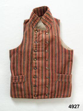 1800 - 1825  Mansväst smalrandig i halvylle. 2 bakstycken, 2 fram-och sidstycken, skörtflikar bak med tränsade förstärkningar av ljusblått lingarn, hög ståndkrage, dubbelknäppning med knapphål på båda framstyckena sydda med mörkblått lingarn samt 8 par släta något kupiga tennknappar, 2 infällda fickor med lister. Helfodrad med treskaftad linnekypert, i ryggen foder av grövre linnelärft, en stor innerficka även den i linnelärft. Östergötland, Finspånga läns hd, Risinge DigitaltMuseum
