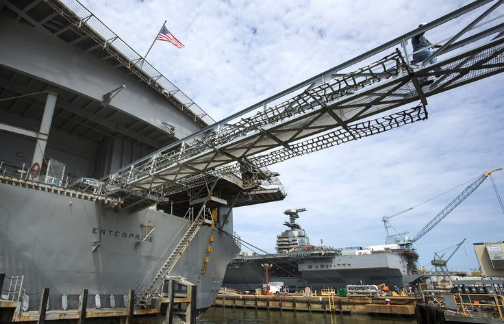 From left, the aircraft carrier Enterprise at the pier at Newport News Shipbuilding Monday, June 30, 2014 with the Navy's newest aircraft carrier the Gerald R. Ford, under construction on the right. (Bill Tiernan | The Virginian-Pilot)