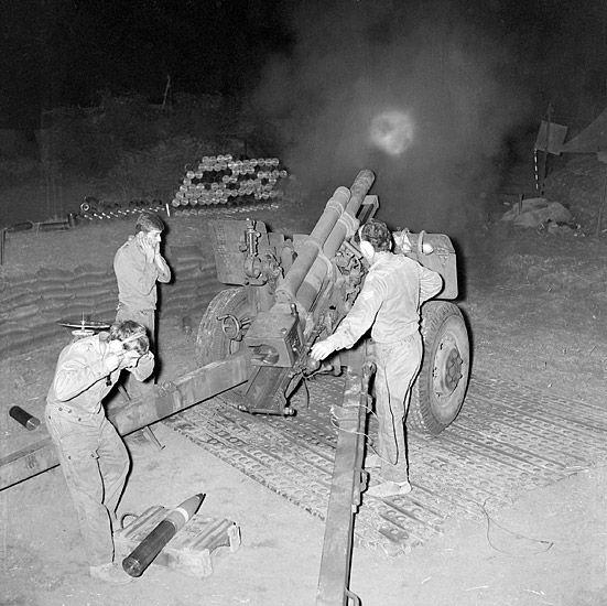 Gunners of the 101st Battery, Royal Australian Artillery fire a 105mm howitzer