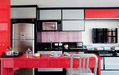 Os armários em tons de cinza, preto e vermelho unem cozinha e sala neste apartamento de 43 m². Repare que, à direita, já fica a bancada da televisão, com marcenaria que pode se desdobrar em escritório. Projeto do designer de interiores Rogério Castro