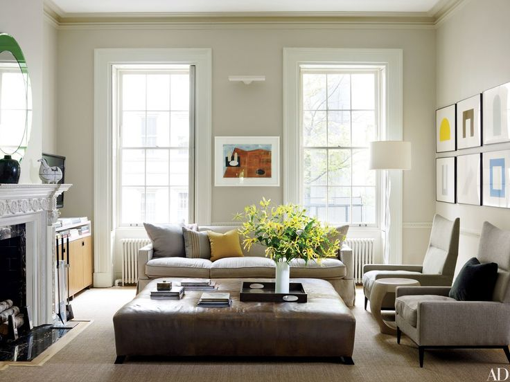 "A Veere Grenney goatskin ottoman anchors the living room of an 1840s <a href=""http://www.architecturaldigest.com/story/leroy-street-studio-christine-markatos-lowe-manhattan-townhouse-article"">Greenwich Village townhouse</a> renovated by the architecture firm Leroy Street Studio and decorated by Christine Markatos Design. Behind the sofa, which is covered in a Donghia fabric, hangs a Jesse Pasca abstract landscape; an R&Y Augousti stool is flanked by Paul McCobb armchairs clad in a Claremo..."