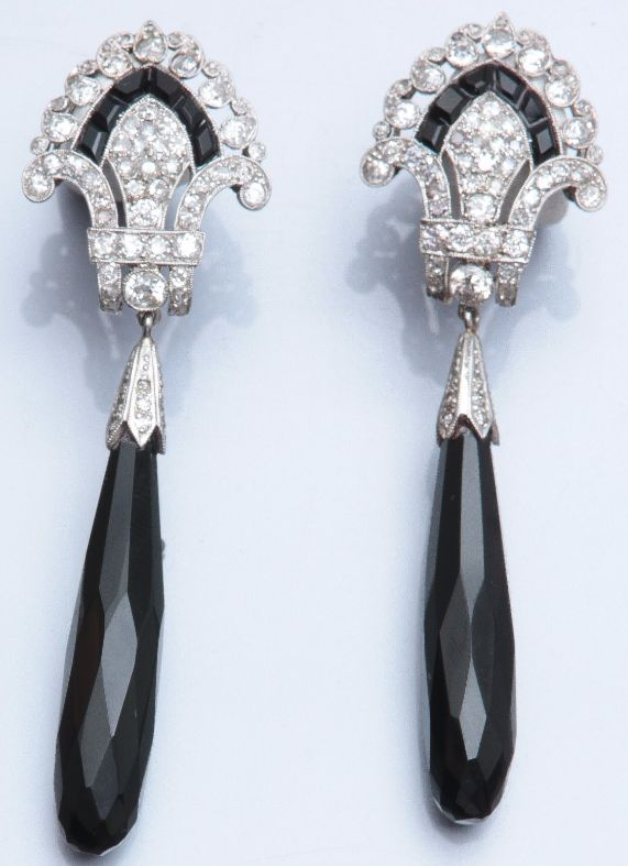 A pair of Art Deco platinum, diamond and onyx earrings, circa 1930. 6.8cm long.