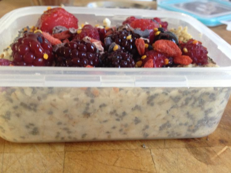 Close up lunch prep. Oatmeal, chia seeds, goji berries, frozen summer fruits, honey, raw cacao nibs and bee pollen!