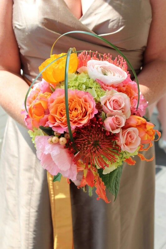 Very Pretty & Colorful Bridesmaid's Bouquet With Pink Roses, Light Pink Ranunculus, Yellow Poppies, Pink Poppies, Pink & Coral Carnations, Coral Pin Cushion Proteas, Pink Snowberry, Orange & Yellow Gloriosa Lilies, Green Hydrangea & Green Bear Grass Looped Over Top The Florals For A Unique & Modern Effect....