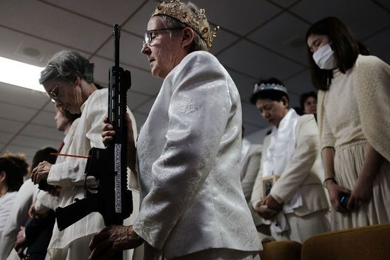 """NEWFOUNDLAND, PA - FEBRUARY 28: A woman holds an AR-15 rifle during a ceremony at the World Peace and Unification Sanctuary in Newfoundland, Pennsylvania on February 28, 2018 in Newfoundland, Pennsylvania. The controversial church, which is led by the son of the late Rev. Sun Myung Moon, believes the AR-15 symbolizes the """"rod of iron"""" in the biblical book of Revelation, and it has encouraged couples to bring the weapons to a """"commitment ceremony"""" or """"Perfection Stage Book of Life…"""
