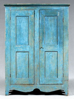 """Pine panel-door cupboard, double panel doors, shelved interior, deeply cut scrolled front and side skirts, early blue paint, pine throughout, cut-nail and circular-saw construction, original hinges, brownish/red paint dry-scraped to reveal early and possibly original blue, one loss to left side molding, proper left rear foot slightly loose, one wooden knob missing, scattered splits, losses and warping, American, probably late 19th century, 73 x 52-1/2 x 20"""""""