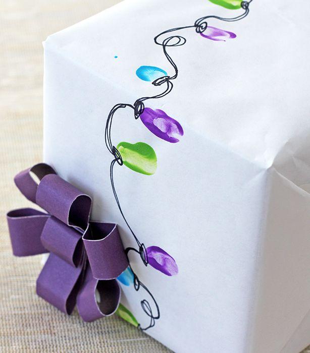 Kids fingertips in paint to make Christmas lights design gift wrap ~