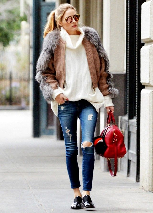 Olivia Palermo wears a ribbed high-neck sweater, faux fur-trimmed cardigan, distressed skinny jeans, oxfords, mirrored sunglasses, and a red satchel