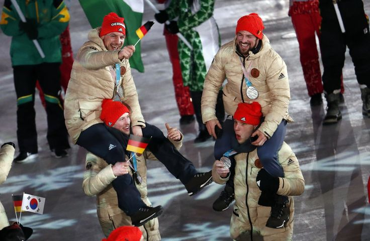 German silver ice hockey players celebrate during the closing ceremony.
