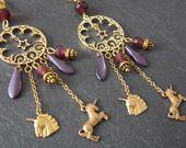 défi d'avril 2014 : hommage à Sandrine. Longues boucles d'oreilles dorées licornes en laiton et perles pourpres, par Seraphina-magie
