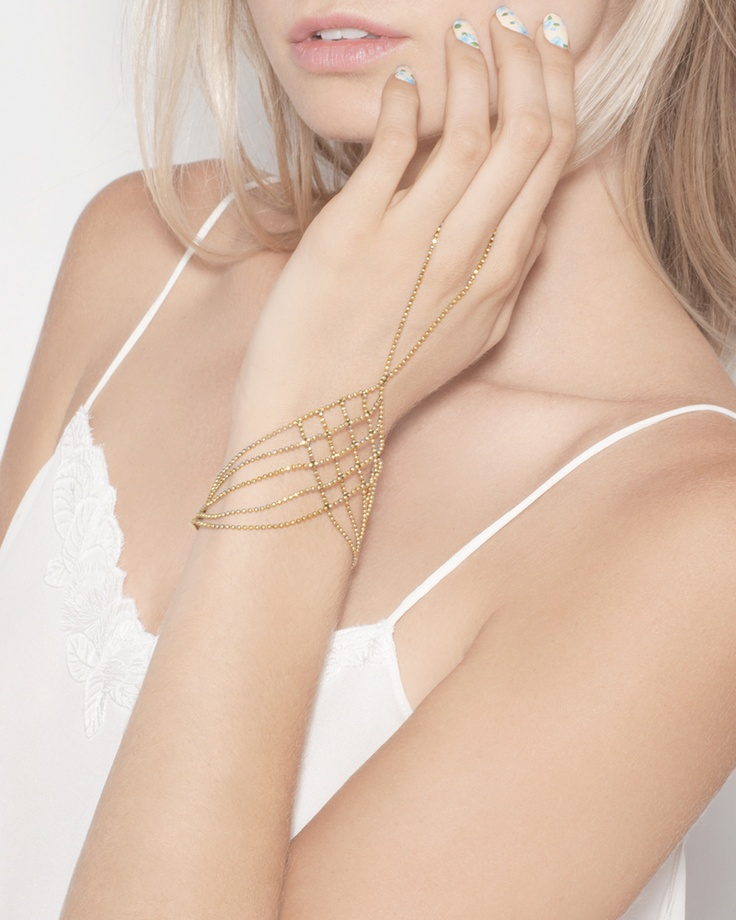 This luxurious hand adornment features woven gold tone chain for a look that's undeniably stunning.