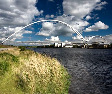 Infinity Bridge - Stockton on Tees, England;  opened in 2009;  named for the infinity symbol formed by its dramatic double curve in reflection on the River Tees;  the main arch is almost 400 feet tall, and the span is nearly 900 feet;  photo by John Devlin / Alamy