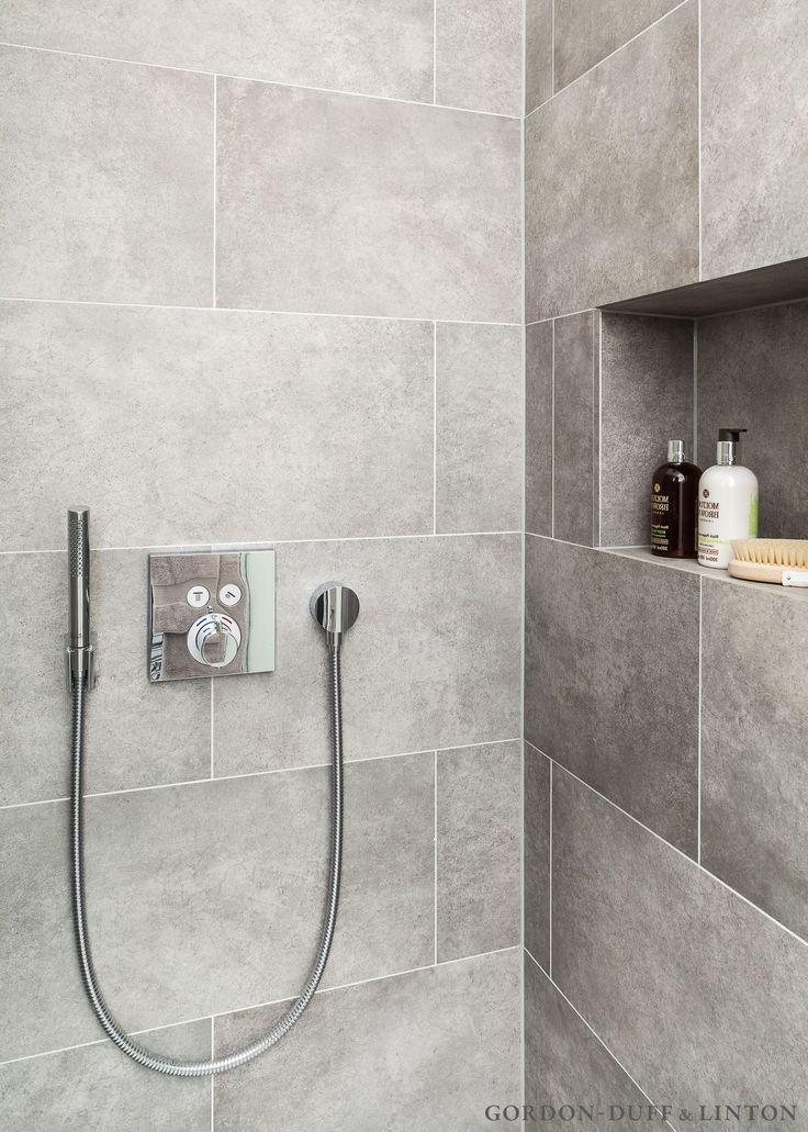 Grey porcelain tiles and shower niche in bathroom. Hansgrohe handshower.