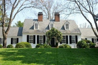 White house, black shutters, vine over the door, dormers, boxwoods...one of my favorite house styles...