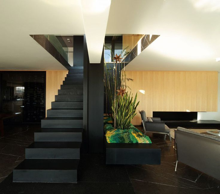 This black steel staircase divides the living and dining spaces in this modern apartment that was created by combining two separate units into one.