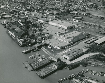 Aerial view of Steveston facing northwest circa 1950's. It is possible to see the Gulf of Georgia bunkhouse, the current Steveston museum building, the Steveston community center and the old tram rail line in the photograph.