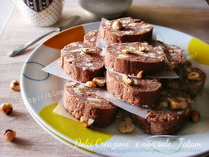 Salame al cioccolato con ricotta e nocciole | senza uovaIngredienti  150 g di cioccolato al latte 180 g di ricotta vaccina 27 g di burro 35 g di zucchero a velo 50 g di nocciole spellate e tostate 150 g di biscotti frollini