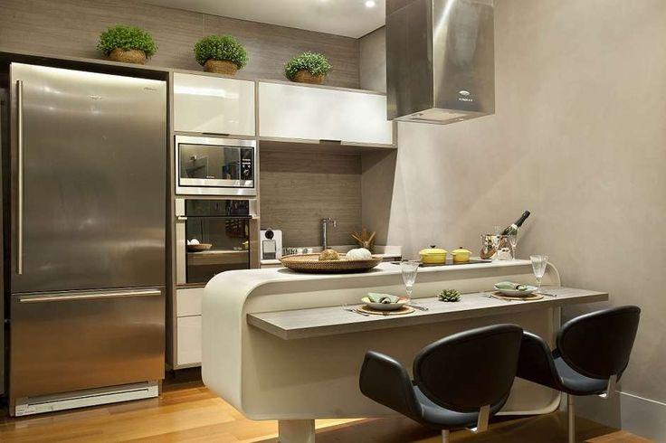 A cozinha projetada por Ana Bartira Brancante é composta por bancada e móveis claros. Os vasos de planta incrementam a decoração. Telefone: (11) 3889-8987